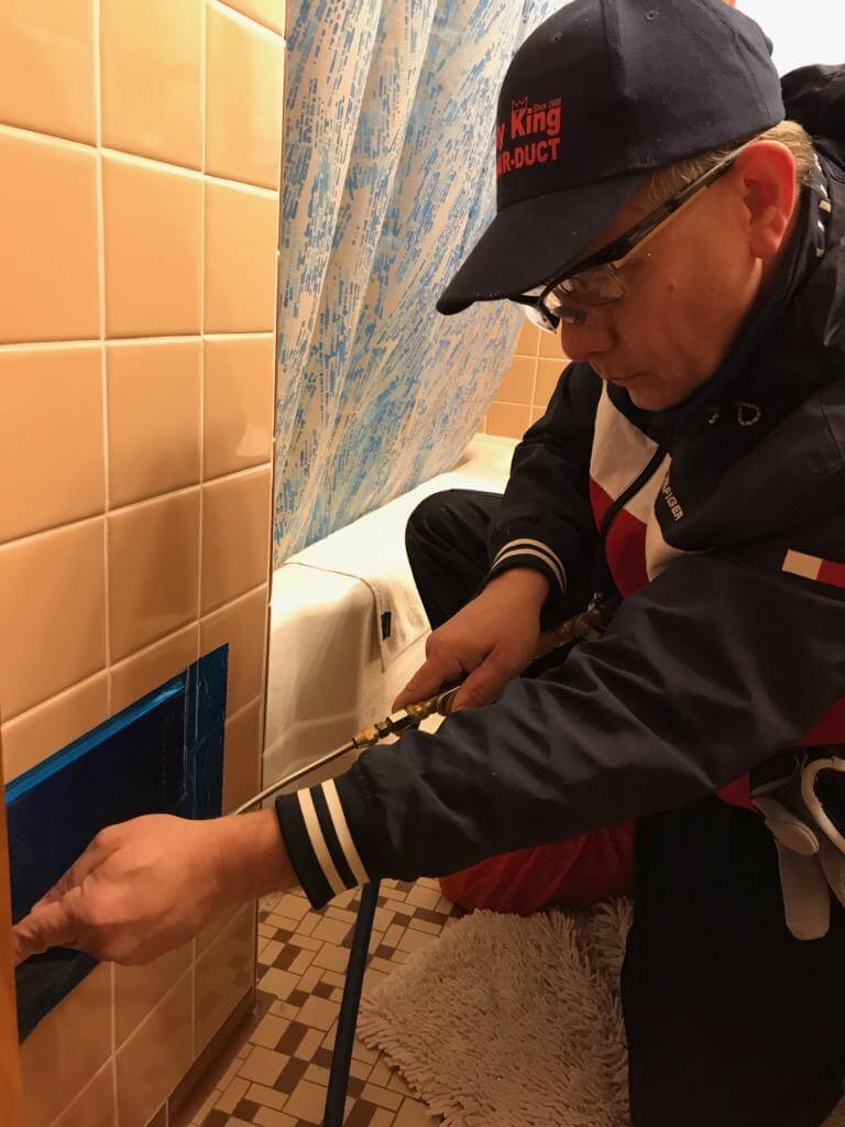 Technician Cleaning a cold air return