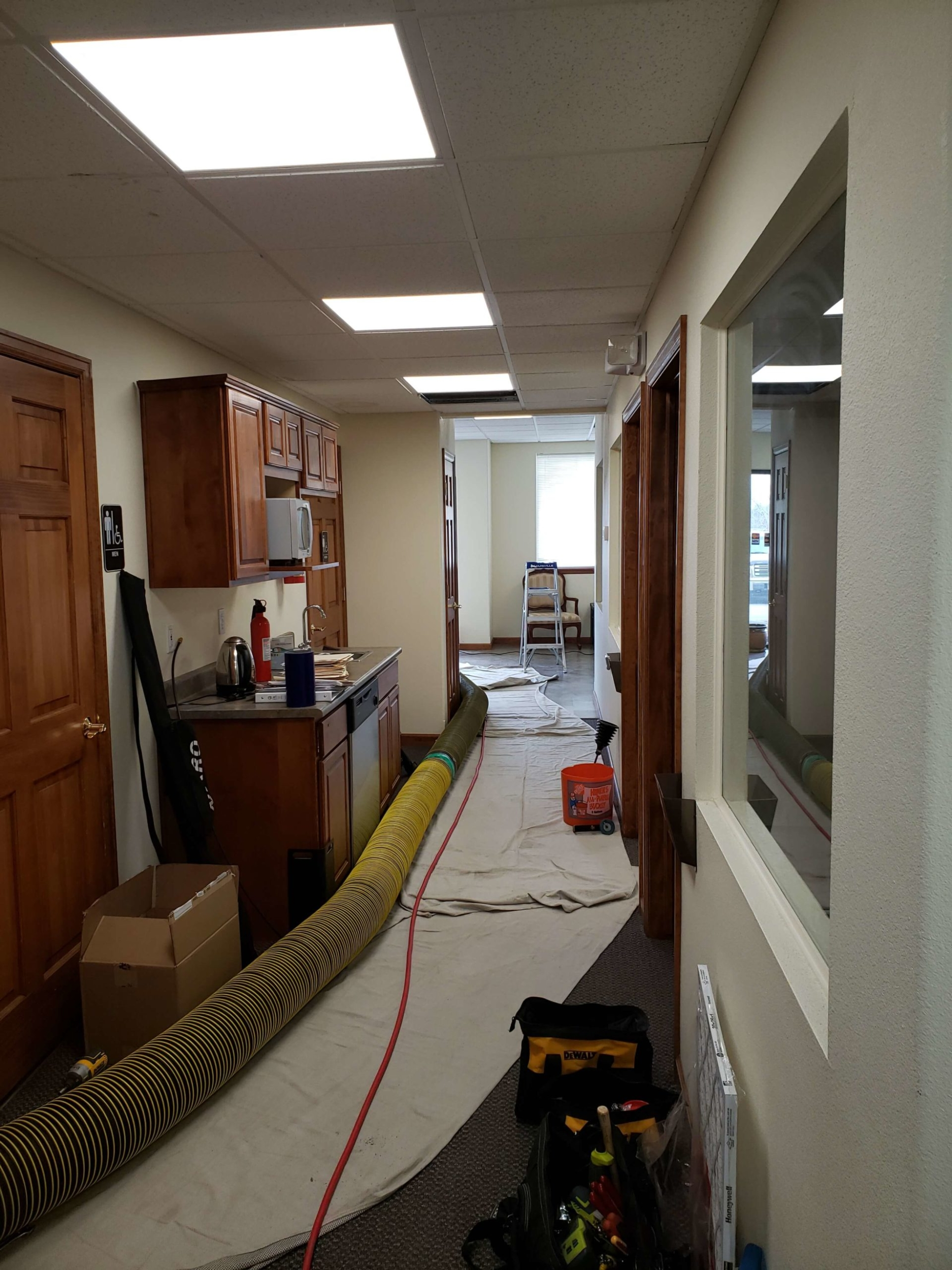 Commercial business hallway with professional HVAC cleaning equipment set up