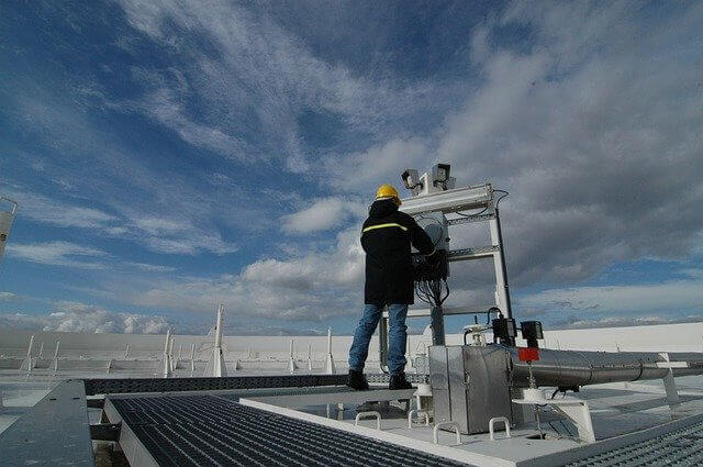 Picture of a man on a roof servicing an industrial air conditioner and HVAC system.